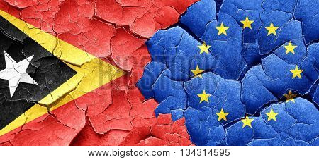 east timor flag with european union flag on a grunge cracked wal