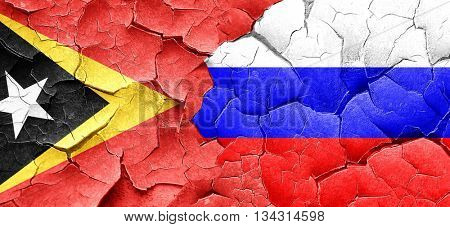 east timor flag with Russia flag on a grunge cracked wall