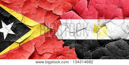east timor flag with egypt flag on a grunge cracked wall