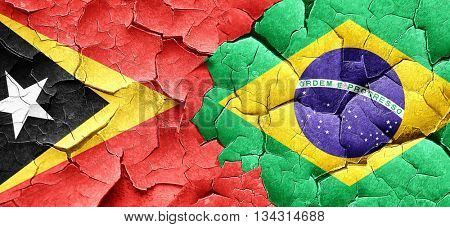 east timor flag with Brazil flag on a grunge cracked wall