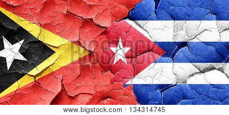 east timor flag with cuba flag on a grunge cracked wall