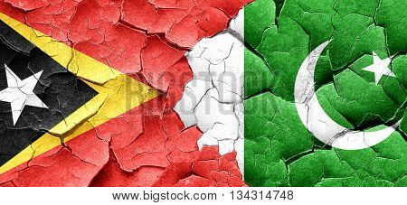 east timor flag with Pakistan flag on a grunge cracked wall