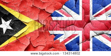 east timor flag with Great Britain flag on a grunge cracked wall
