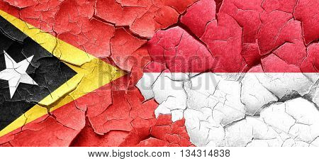 east timor flag with Indonesia flag on a grunge cracked wall