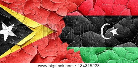 east timor flag with Libya flag on a grunge cracked wall