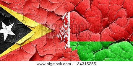 east timor flag with Belarus flag on a grunge cracked wall
