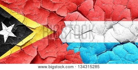 east timor flag with Luxembourg flag on a grunge cracked wall