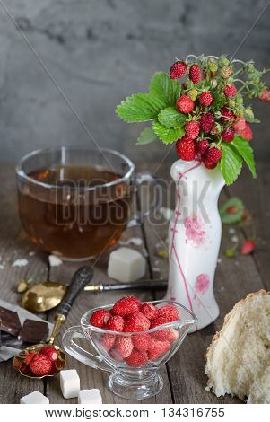 Strawberries in a glass Cup and a bouquet of wild strawberries in a vase. White bread crumb, antique spoons and tea, rustic Style, background blur.