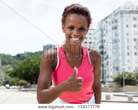 Beautiful african american girl in pink shirt showing thumb in city in the summer