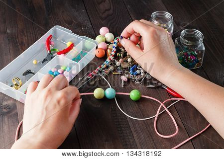 Pair Of Hands And Pliers Assembling A Bead Necklace.