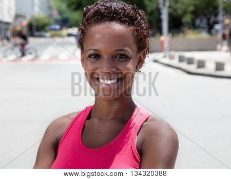 African american girl in pink shirt in city in the summer