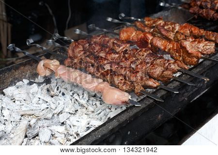 Raw kebab grilling on metal skewer. Raw meat roasting at barbecue. BBQ fresh beef and chicken meat chop slices. Traditional eastern dish, shish kebab. Grill on charcoal and flame, picnic, street food