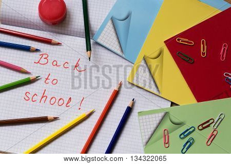 Back to school . School supplies on the background of notebook sheet in a cage