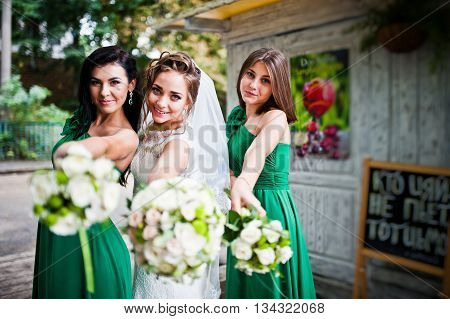 Thre Charming Bride And Bridesmaids Showing Wedding Bouquets At They Hands
