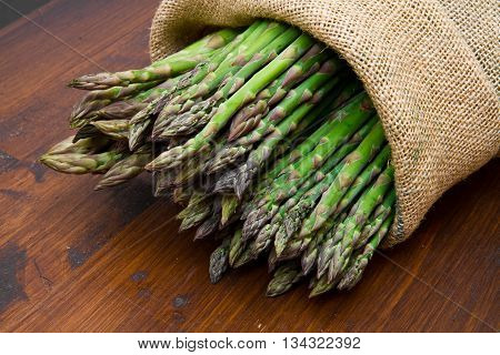 group of asparagus in burlap sack on wood