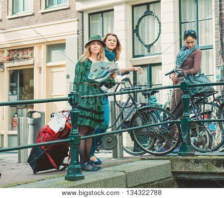 Three female tourists walking through narrow Amsterdam streets