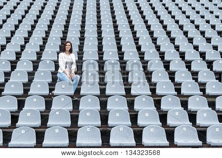 Lonely beautiful woman sitting on a gray empty stadium tribunes in the rain