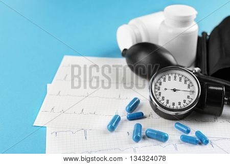 Medical manometer, pills and cardiogram on blue background