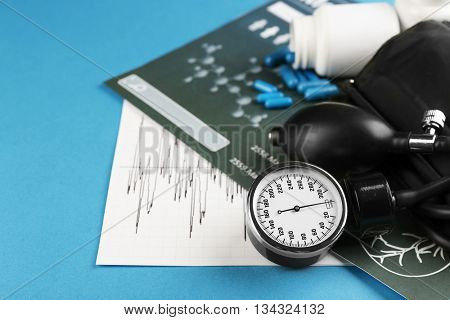 Medical manometer, pills and medical record on blue background