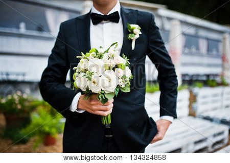 Wedding Bouquet At Hand Of Groom With Bow Tie
