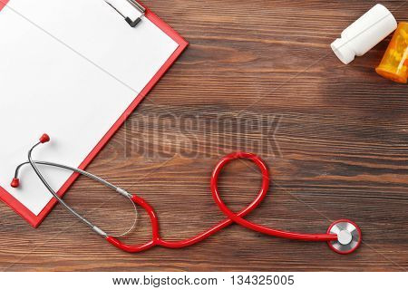 Red stethoscope with prescription on wooden background