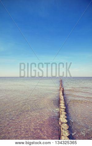 Vintage toned an old wooden breakwater in sea.