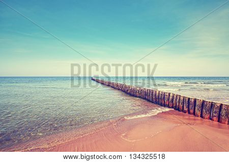 Retro Toned Beach With Old Wooden Breakwater