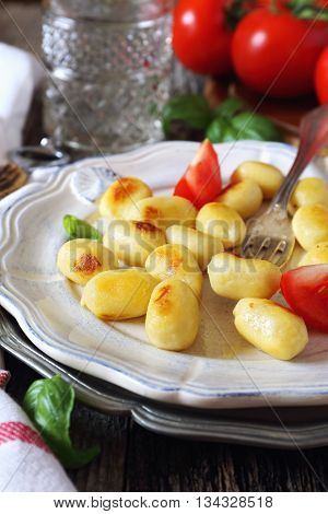 Italian cuisine: fried potato gnocchi with cheese and tomatoes