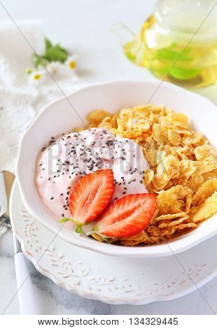 Healthy breakfast: corn flakes in bowl yogurt strawberries and chia seeds
