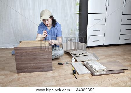 Assembling home furniture woman carpenter hardboard attached to a wooden frame nightstand tightening screw with a turn-screw.