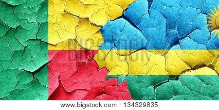 Benin flag with rwanda flag on a grunge cracked wall