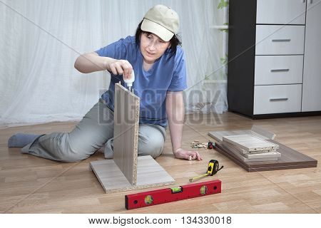 Woman putting together self assembly furniture assemble flat pack.