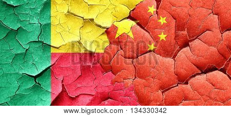 Benin flag with China flag on a grunge cracked wall