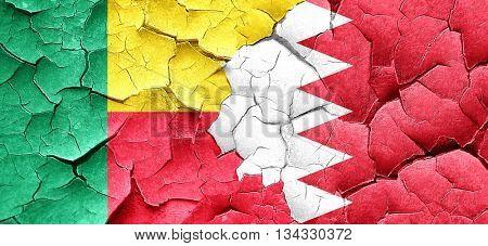 Benin flag with Bahrain flag on a grunge cracked wall