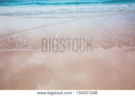 Tropical Bermuda beach with surf and reflections of the sky on the wet sand.