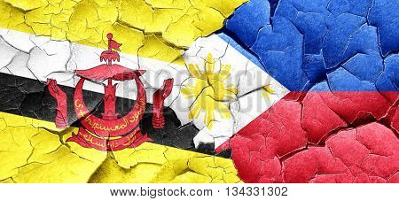 Brunei flag with Philippines flag on a grunge cracked wall