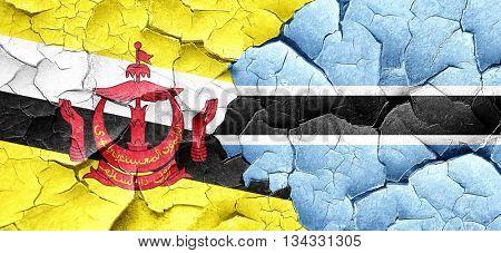 Brunei flag with Botswana flag on a grunge cracked wall