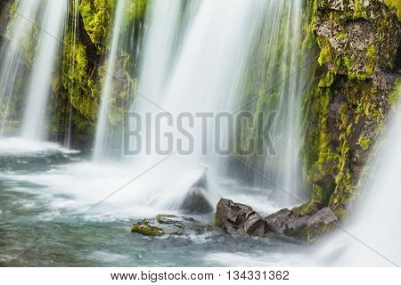 Summer day in the cold Iceland. Powerful cascading waterfall on the mossy cliff
