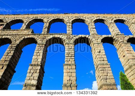 Upward View Of The Roman Aqueduct Of Segovia, Spain Under Blue Skies