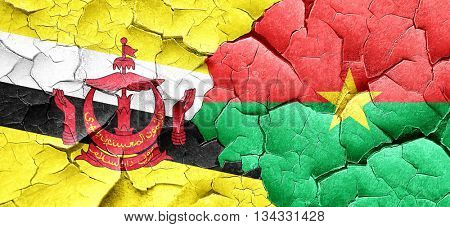 Brunei flag with Burkina Faso flag on a grunge cracked wall
