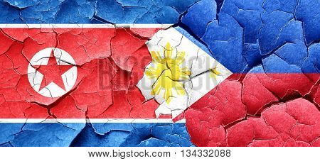 North Korea flag with Philippines flag on a grunge cracked wall