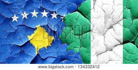 Kosovo flag with Nigeria flag on a grunge cracked wall