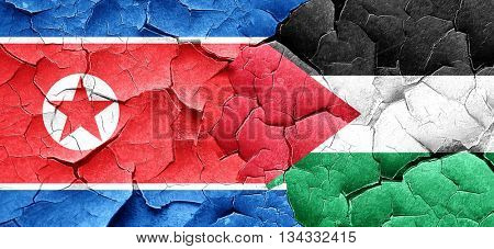 North Korea flag with Palestine flag on a grunge cracked wall