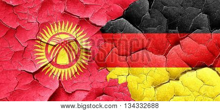 Kyrgyzstan flag with Germany flag on a grunge cracked wall