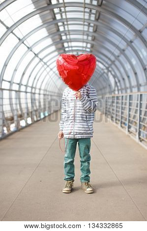boy with red heart instead of a face. child hid his face behind a balloon in the shape of heart.  boy holding a red balloon in front of his face. concept of love