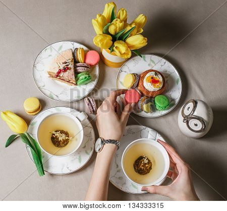 Green tea, macaroon, different cakes. Fresh breakfast table. Top view. Concept of business or holiday breakfast.
