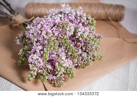 Empty postal envelope and bouquet of lilac flowers on the white wooden background, copy space. Top view