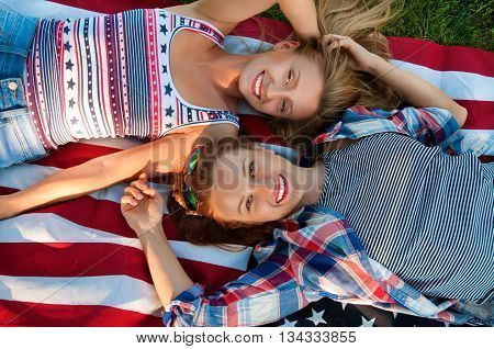 Young happy patriot women celebrating independence day 4th of july on the united states flag