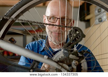 a man repairing bike gear in his workshop.