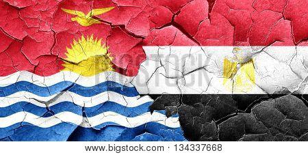 Kiribati flag with egypt flag on a grunge cracked wall